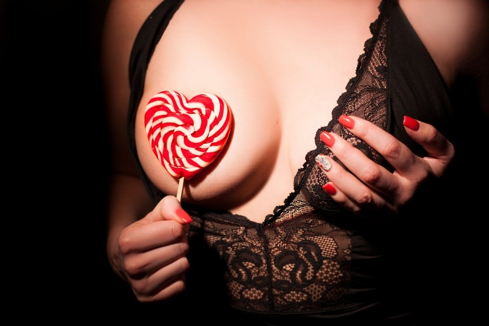 woman holding up candy to her boobs
