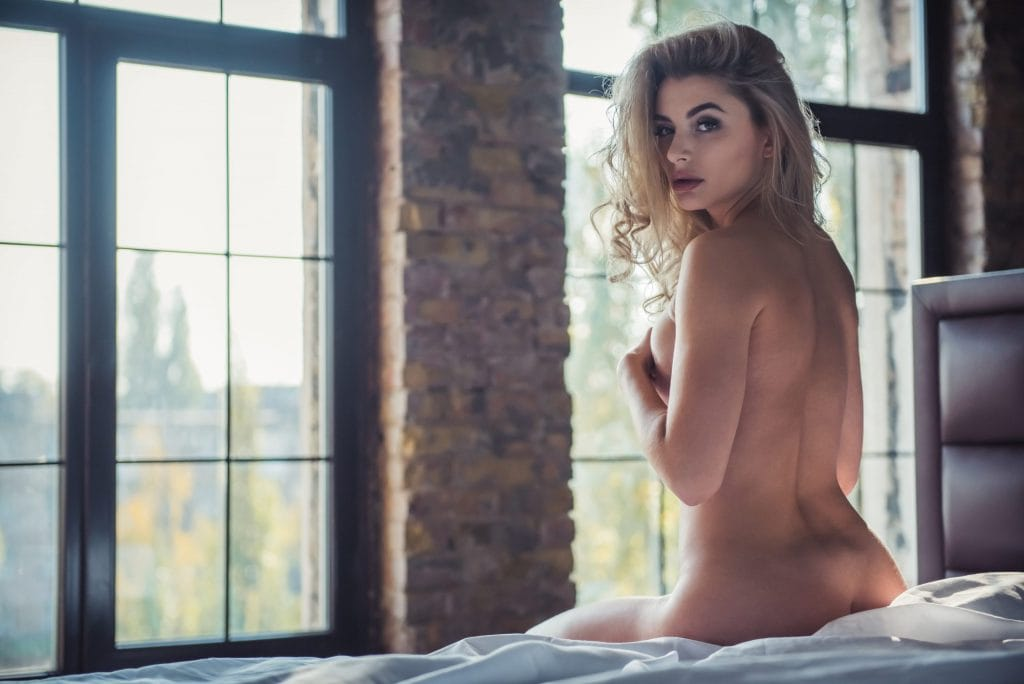 sexy naked woman sitting on bed