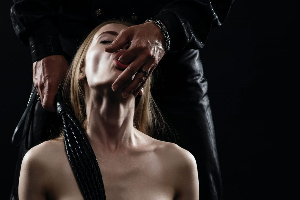 Hot BDSM couple with whip
