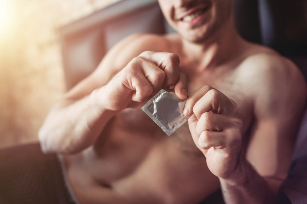 man unwrapping condom