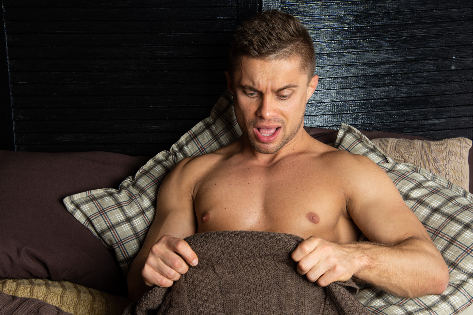 man looking down at his penis in bed