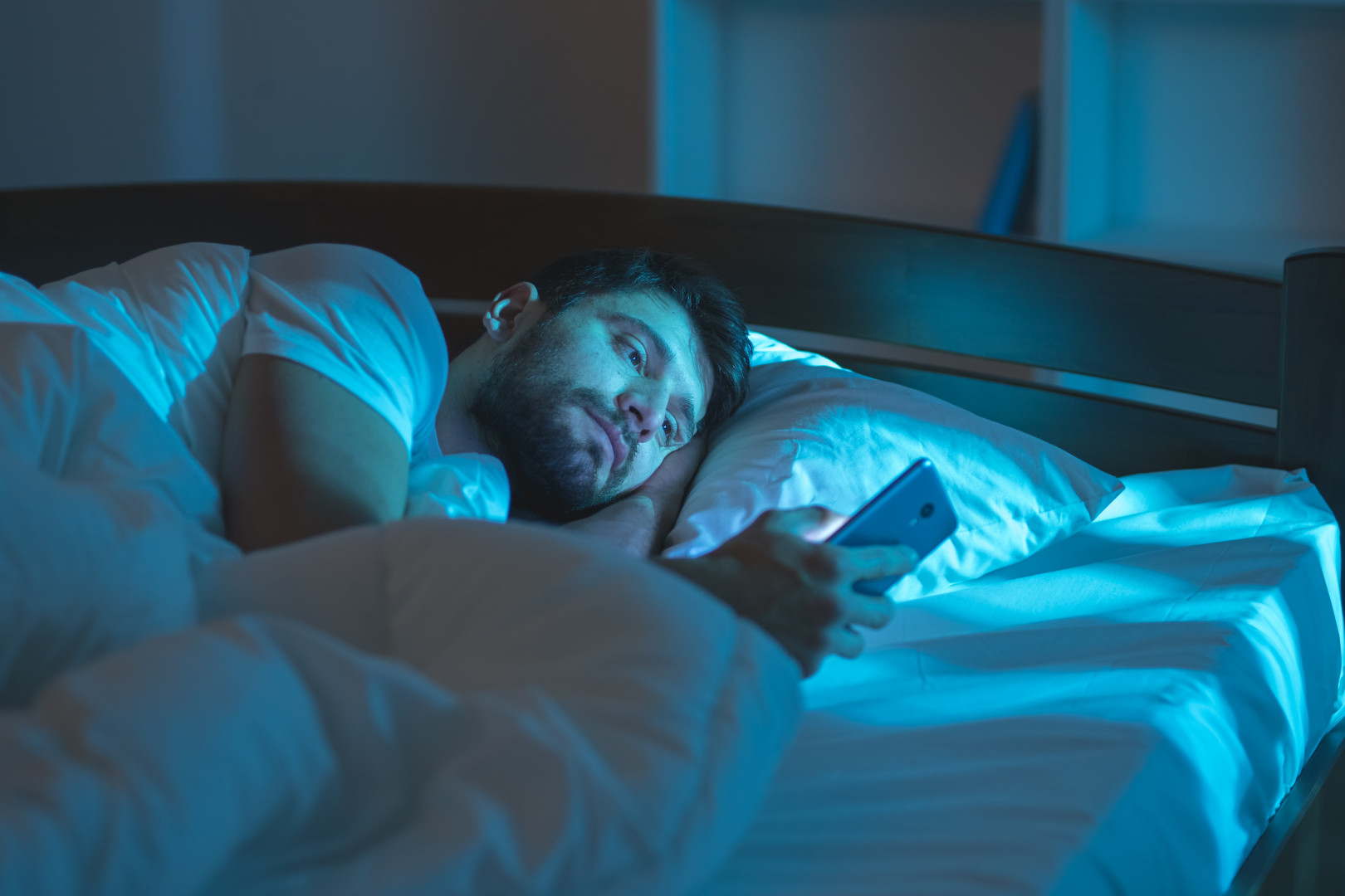 Lonely man looking at phone in bed
