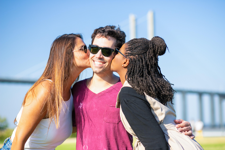 two women kissing one man