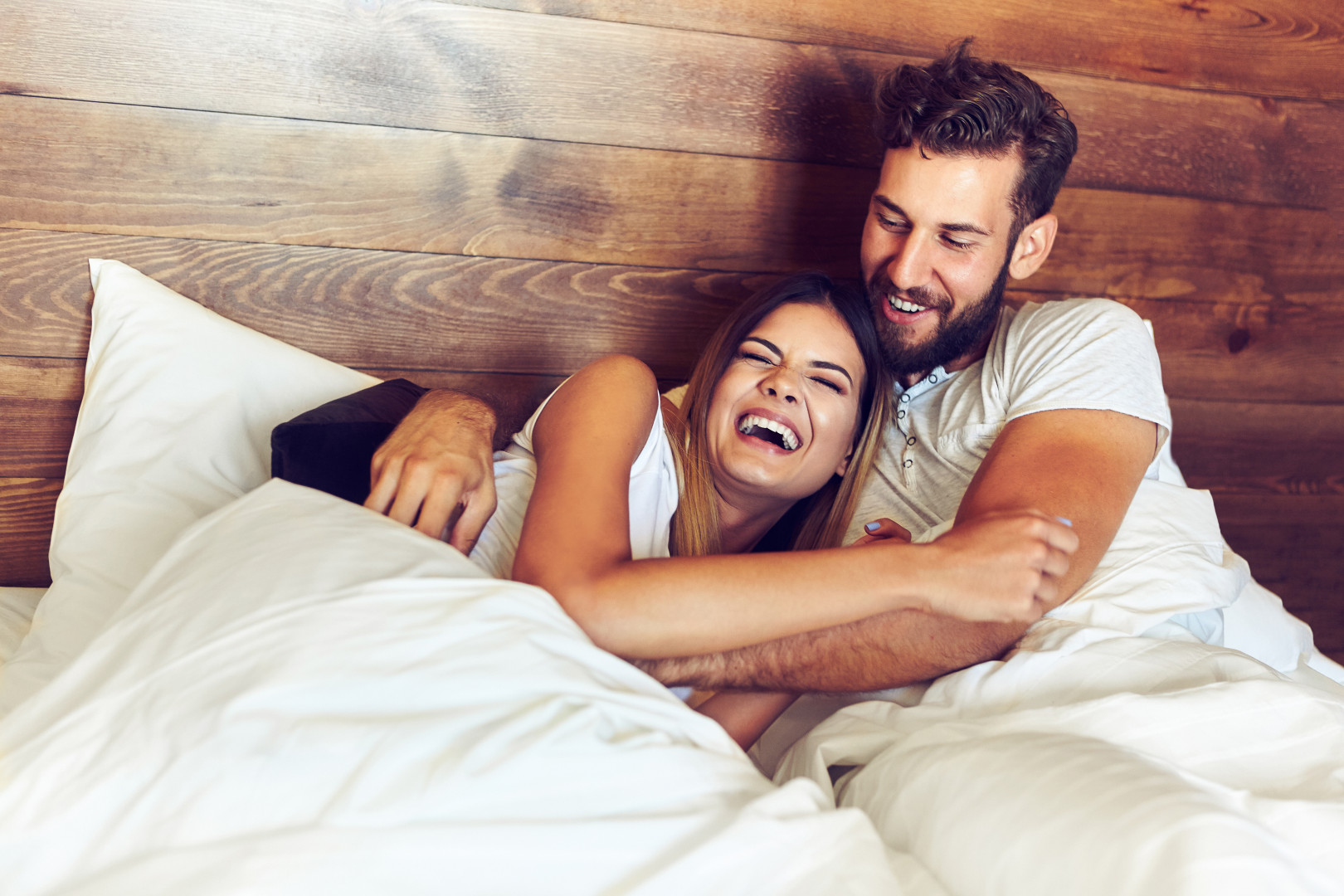 couple laughing together in bed