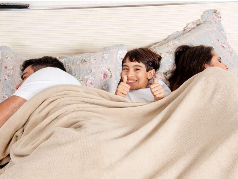 toddler between parents in bed