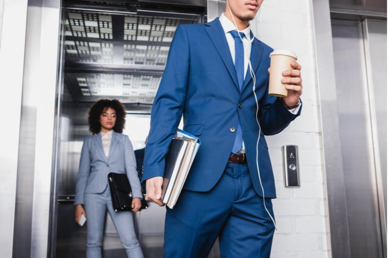 Businessman in earphones with coffee cup walking from elevator with businesswoman