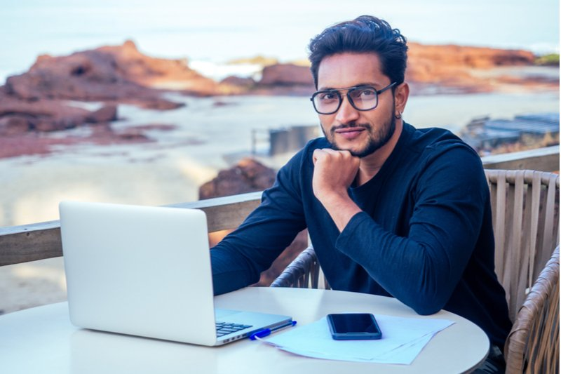 Handsome and successful Indian man in a stylish outfit working with a laptop on the beach. Alpha Male