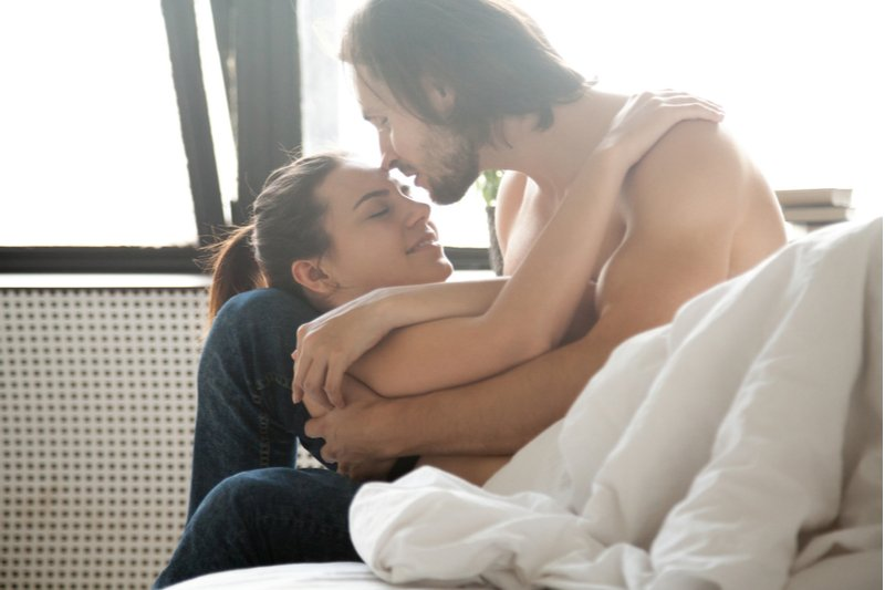 Man and woman cuddling in bed while kissing.