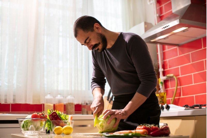 Man cooking his favorite meal to ground himself from the feelings of jealousy.