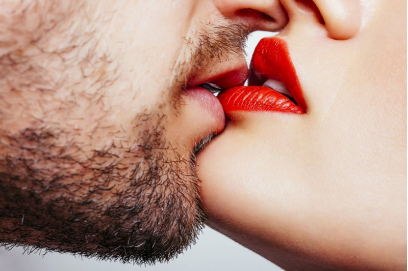 Man and woman's lips touching before a kiss.