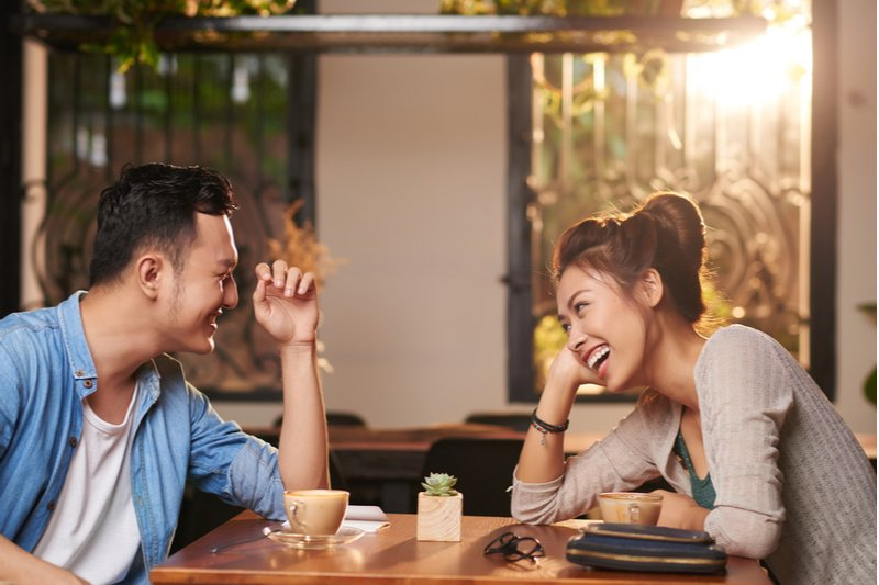Young man and woman are attracted to each other's mindsets. They were sitting in a cafe drinking coffee and laughing.