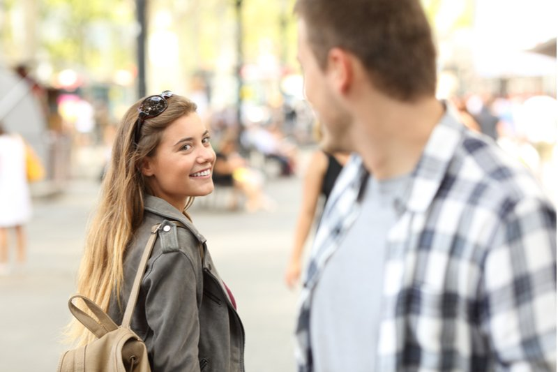 Woman looking back at the man in a flirtatious manner.