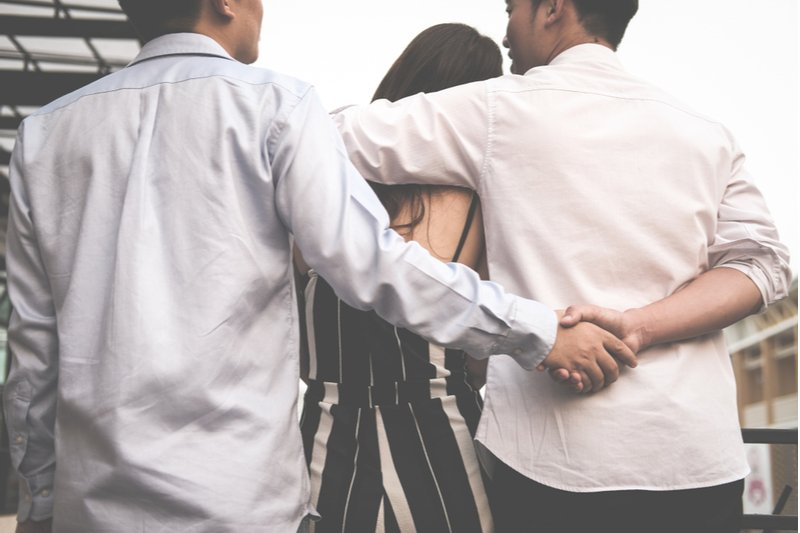 homosexual man hug woman while holding hands with another lover.