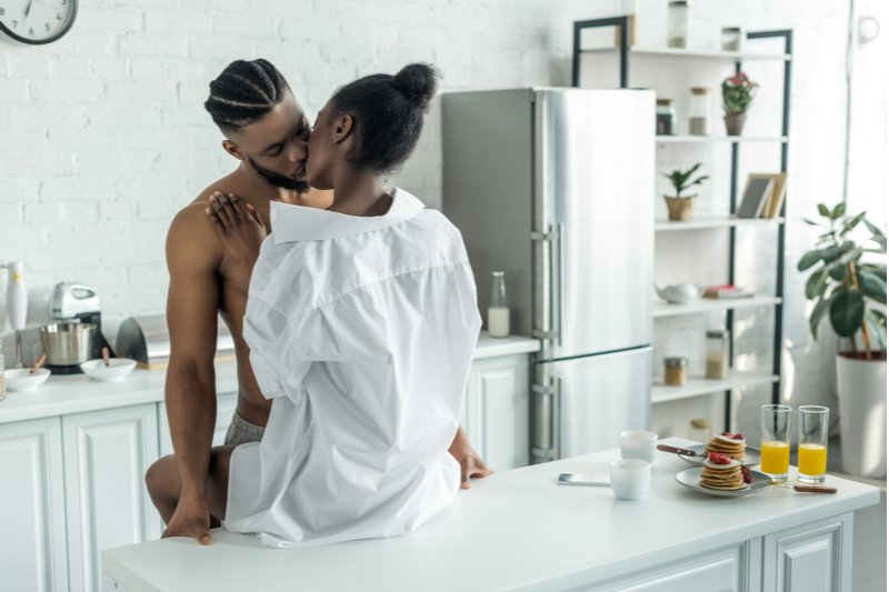 Man and woman kissing romantically in the kitchen.