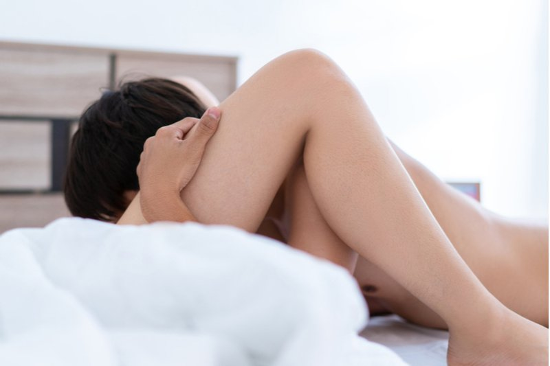 Man pleasuring a woman by performing oral sex so he can last longer in bed.