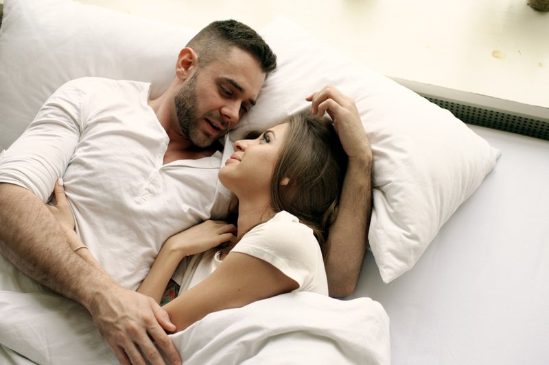 Man talking to woman in bed