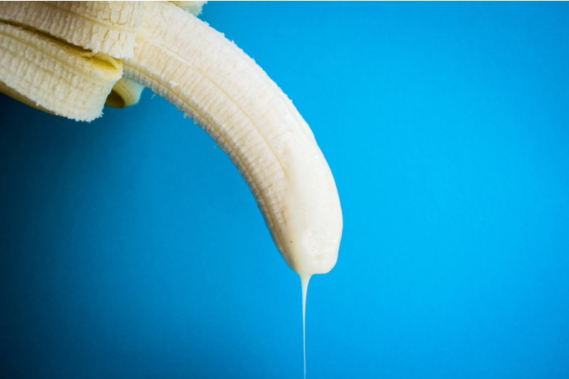 Banana with condensed milk resembling a penis dripping in semen.