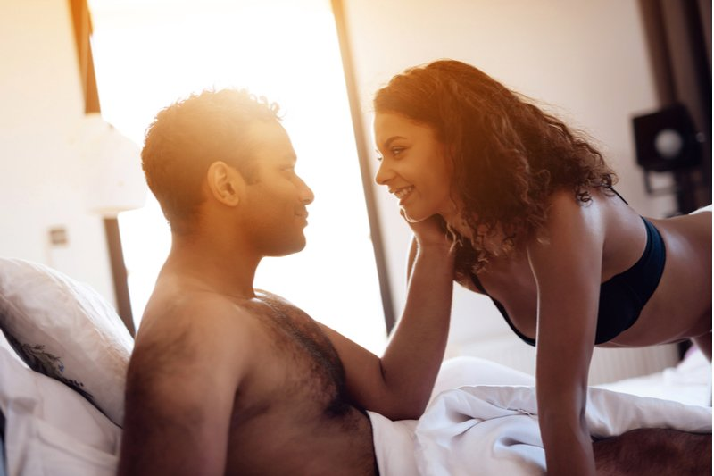 Man and woman in bed about to spice things up in the bedroom.